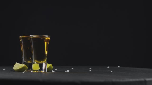 two glasses with golden tequila on a black background on a rotating black board. coarse salt falls on top of tequila. alcoholic drinks at the bar. close-up shot. 4k video. 59.94 fps - rum superalcolico video stock e b–roll