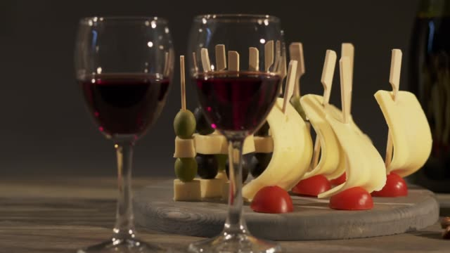 Two glasses with red wine, grapes and cheese skewers on wooden tray