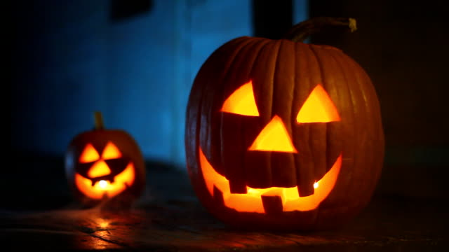 Two glowing jack-o-lanterns with eerie smoke, ready for Halloween video