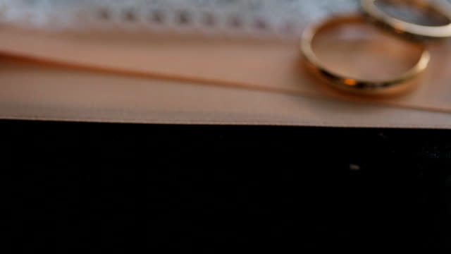 Two golden bridal rings lies on black table video