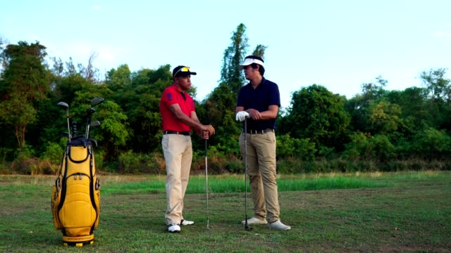 Two golfers are talking on the training ground