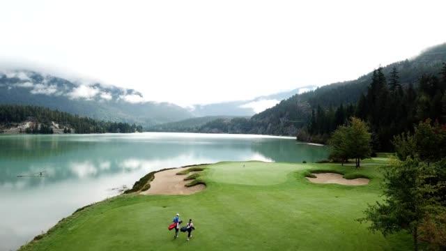 vidéos et rushes de deux golfeurs marchant approchant du putting green - golf