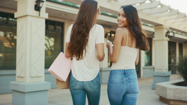 Two gorgeous friends have golden smiles and shopping bags for miles