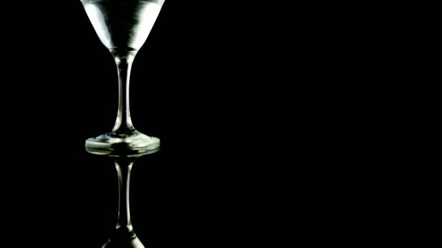 Two green olives falling in the cocktail glass video