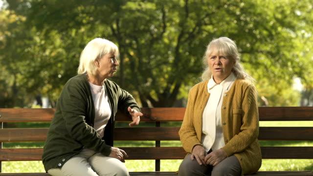 två griniga gamla damer att döma förbipasserande personer, som sitter på bänken i parken, pension - dom bildbanksvideor och videomaterial från bakom kulisserna