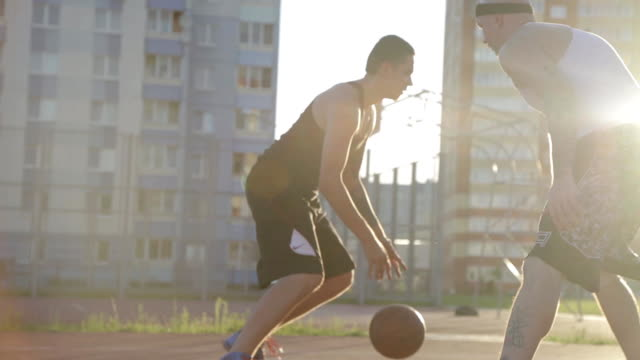 Two guy play basketball at district sports ground in a backlit sun on the background of residential buildings.