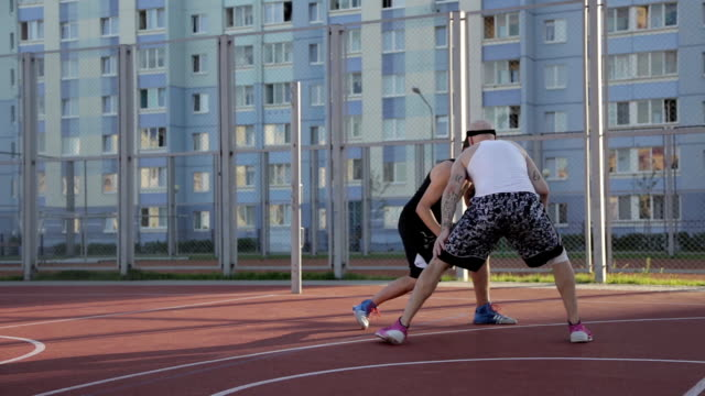 Two guy play basketball at district sports ground.