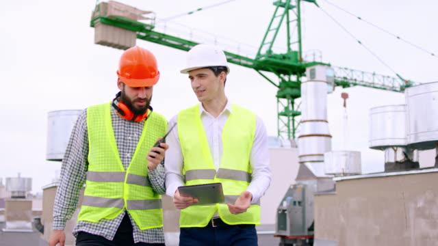 två kille med skyddshjälmar en affärsman och en av killen är huvudsakliga konstruktion går genom taket och analysera planen för byggarbetsplatsen med hjälp av digital tablett - bordsjordglob bildbanksvideor och videomaterial från bakom kulisserna