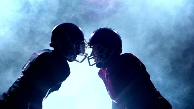 två killar fotbollsspelare inför sina hjälmar i röken. slow motion - bum bildbanksvideor och videomaterial från bakom kulisserna