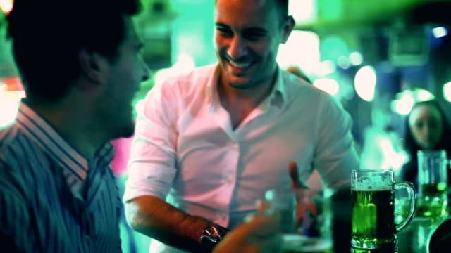 Two guys having fun in a bar and drinking beer. Two early 30's adult men having beer in a local bar on a friday night. Having casual conversation, laughing and having fun after work. Wearing casual shirts and leaning against bar counter. bar counter stock videos & royalty-free footage