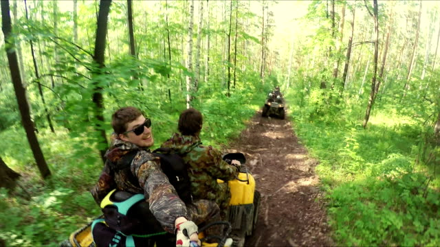 Two guys on quad ride through the forest video