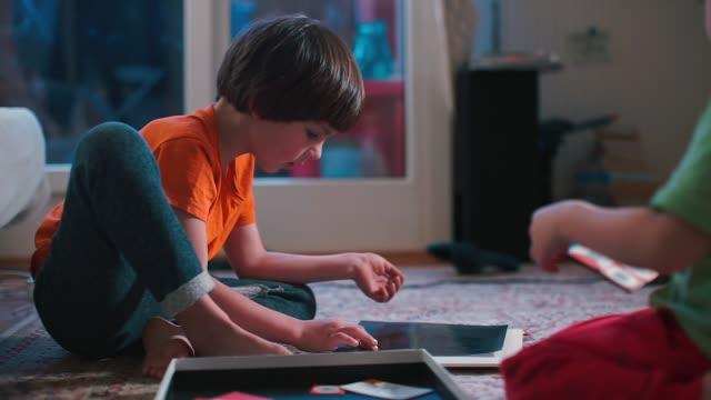 vídeos y material grabado en eventos de stock de dos tipos juegan un juego de mesa en el suelo. - tablón