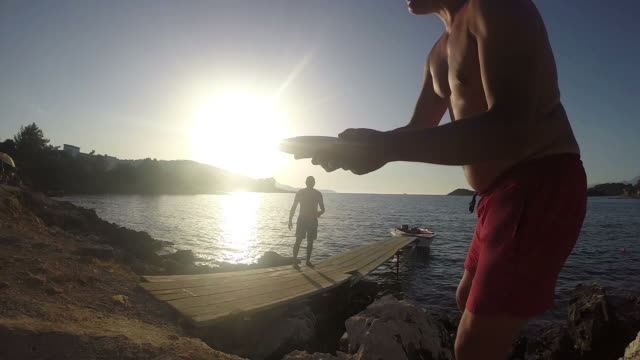 Two guys playing Frisbee together in shorts at sunset ocean pier, SLOW MOTION stock video video