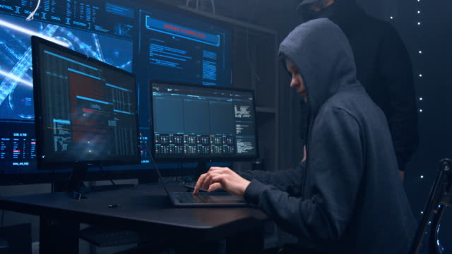 Two hackers in hoodies work on a computers with maps and data on display screens in a dark office room. Two hackers in hoodies work on a computers with maps and data on display screens in a dark office room. russian ethnicity stock videos & royalty-free footage