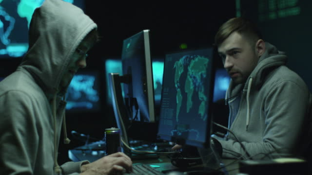 Two hackers in hoodies work on a computers with maps and data on display screens in a dark office room. video