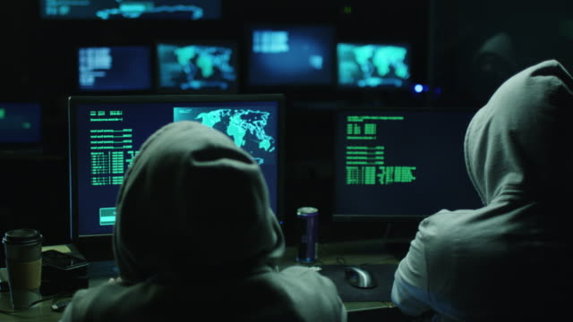 Two hackers in hoods work on a computers with maps and data on display screens in a dark office room. Two hackers in hoods work on a computers with maps and data on display screens in a dark office room. Shot on RED Cinema Camera in 4K (UHD). hacker stock videos & royalty-free footage