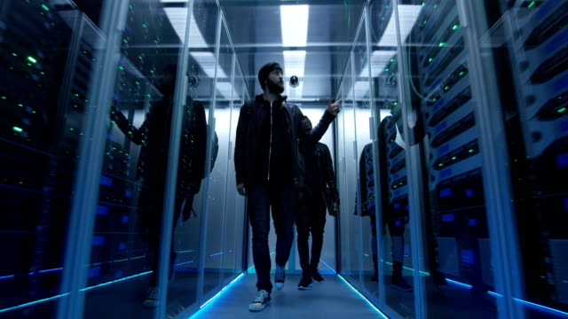Two hackers walking through rows of servers Wide shot of a two hackers walking through corporate data center with rows of working rack servers server room stock videos & royalty-free footage