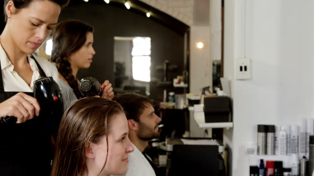 Two hairdresser blow drying their client hair video