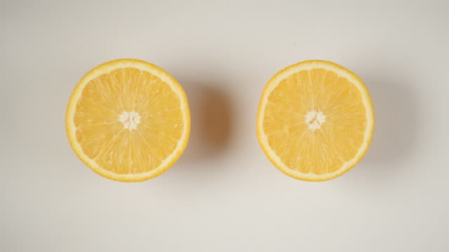 TOP VIEW: Two half of an orange are swinging on a white table video