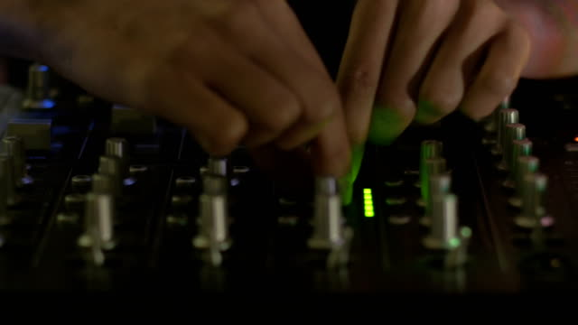 Two hands make adjustments on a DJ mixing console - CU dolly