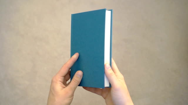 Two hands opening a blank book.