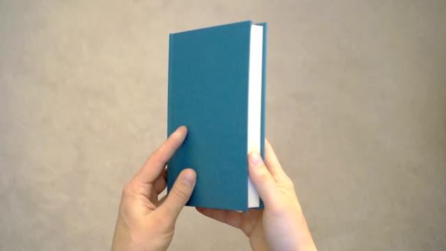 vídeos y material grabado en eventos de stock de dos manos de abrir un libro blanco. - libro
