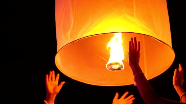 slo mo two hands release floating sky lantern to the sky - китайский фонарь стоковые видео и кадры b-roll