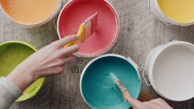 two hands taking paint from bucket with paintbrush - vivid 4k video stock videos & royalty-free footage