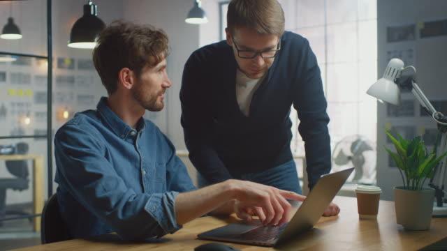due bei colleghi creativi parlano di opere e ne discutono su un computer portatile nel loro ufficio sunny loft. sembrano fighi e hanno la barba. office ha una grande finestra con una vista urbana sulla città. - abbigliamento casual video stock e b–roll