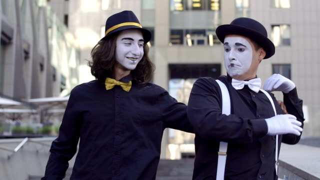 Two handsome mimes in hats The mimes in hats have fun in front of camera. Urban actors are posing for camera. Man with long hair hug his friend holding him by the shoulder, but his friend don't like it. greasepaint stock videos & royalty-free footage