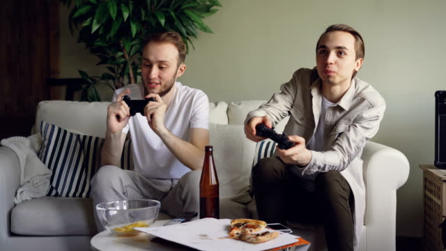 Two handsome young guys are playing videogame holding joysticks sitting on sofa at home. Emotional men are enjoying game, snacks and bottles are visible. video