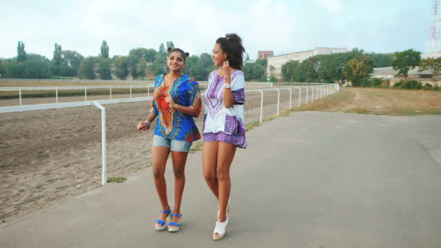 Two happy beautiful afro-american women friends walking outdoor. Young mixed race girls wearing colorful clothing communicates, enjoys the meeting and laughing in slow motion. Dolly shot video