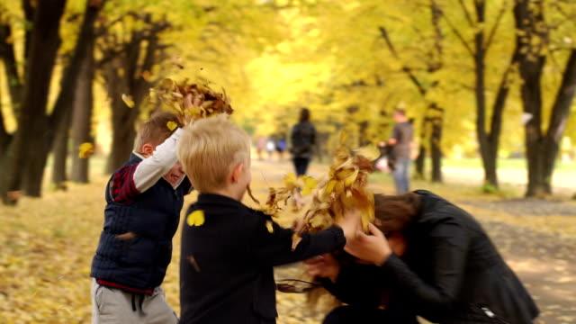 vídeos de stock e filmes b-roll de two happy boys throw yellow leaves at their mother in the autumn park. - passagem de ano
