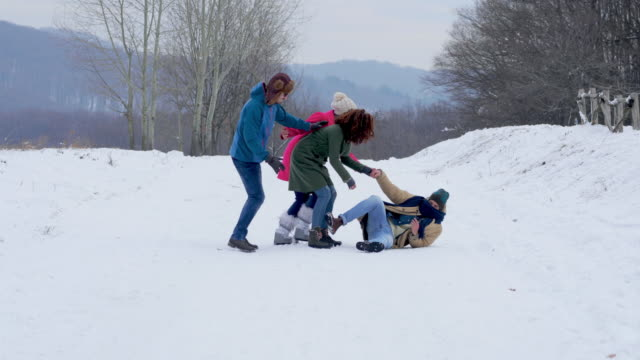 Two happy couples taking a walk on a snow in nature. Group of smiling friends walking in winter park. One man fell on snow while the others are helping him to stand up. misfortune stock videos & royalty-free footage