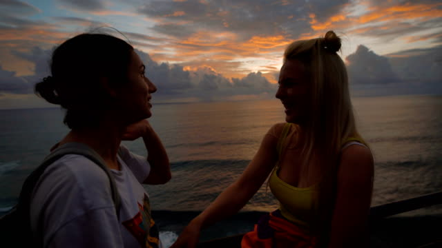 two happy female travelers talking and laughing at the sunset against a background of the sea. blonde and brunette are chattering and smiling looking at waving ocean behind them - maglietta bianca video stock e b–roll