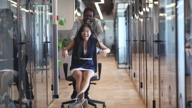 Two happy funny diverse coworkers ride chair in office hall