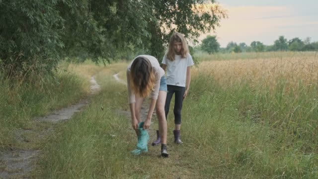 two happy girls sisters walking after rain in dirty clothes children talking laughing, fun pouring water from their boots, rural road summer nature background - imperfection stock videos & royalty-free footage