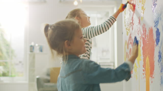 Two Happy Little Girls with Hands Dipped in Colorful Paint Put Handprints and Draw on the Wall. They are Having Fun and Laugh. Home is Being Renovated.