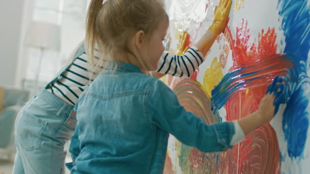 Two Happy Little Girls with Hands Dipped in Colorful Paint Put Handprints and Draw Abstractions on the Wall. They are Having Fun and Laugh. Home is Being Renovated.