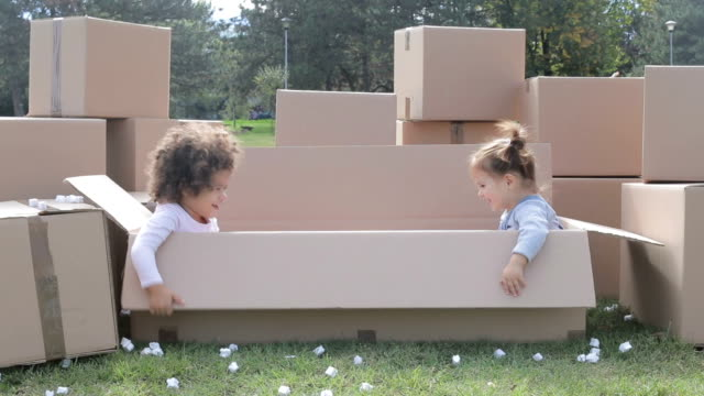 two happy multicultural babies having fun in cardboard boxes and playing hide and seek - new home stock videos & royalty-free footage