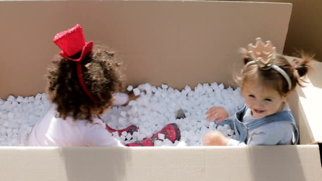Two happy multicultural babies having fun in cardboard boxes , holding head bands ,hat and crown video