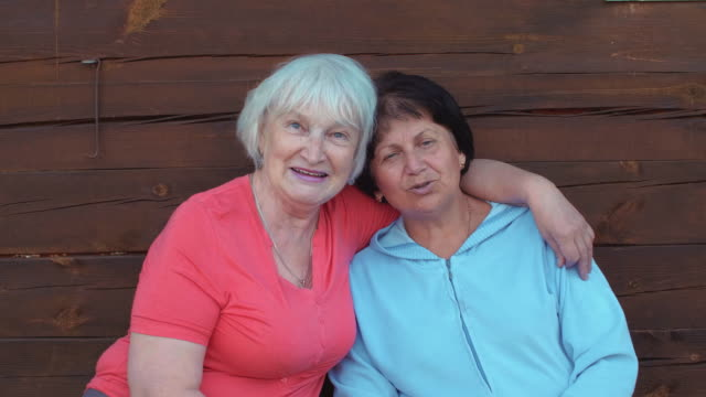 Two happy senior woman embracing and cheerfully speaking front camera Two happy senior woman embracing and cheerfully speaking front camera. Smiling and happy elderly women on wooden background sister stock videos & royalty-free footage