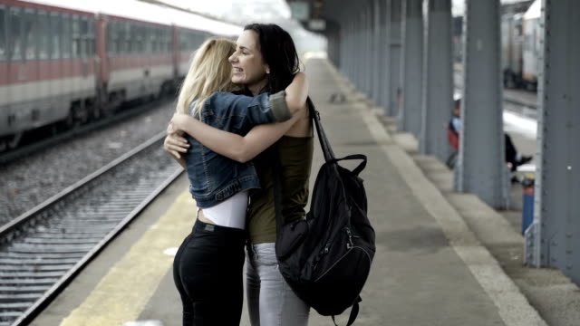Two happy teen girls reunited in train station hugging and walking home hand in hand video