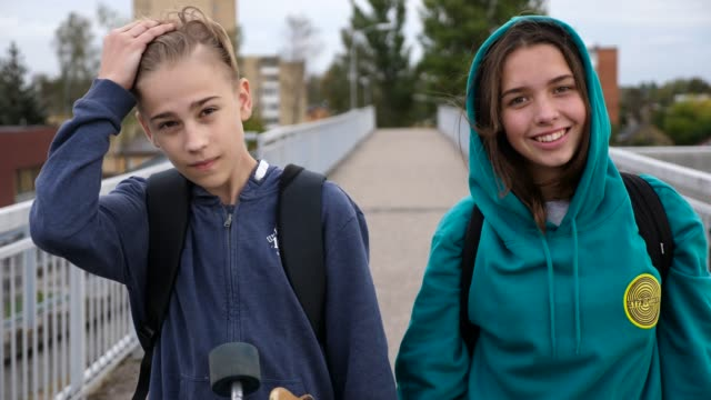 two happy teenagers standing on the bridge smiling and dabbing to camera, close up