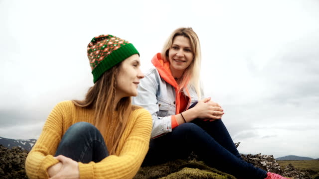 Two happy woman sitting on the lava field covered moss in Iceland and talking. Tourists friends resting after hiking