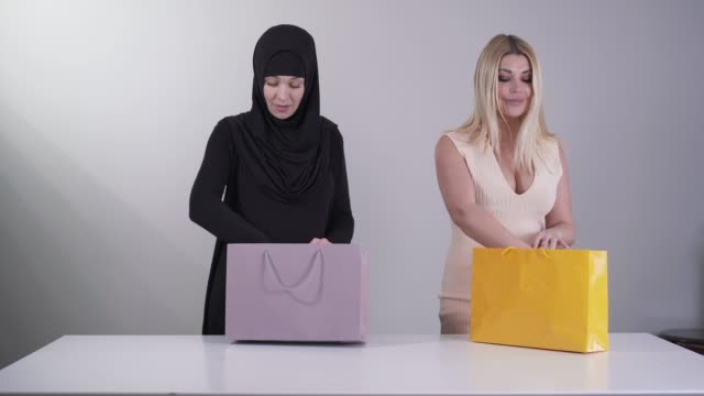 two happy women coming with shopping bags and taking out new dresses. modern caucasian woman holding dress with sparkles as conservative muslim woman enjoying new black traditional clothes. - abbigliamento religioso video stock e b–roll