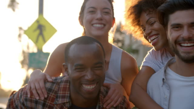 Video Two happy young adult couples piggybacking the street