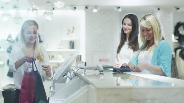 2 つの幸せな若い女の子は、デパートのレジで服を買っています。 ビデオ