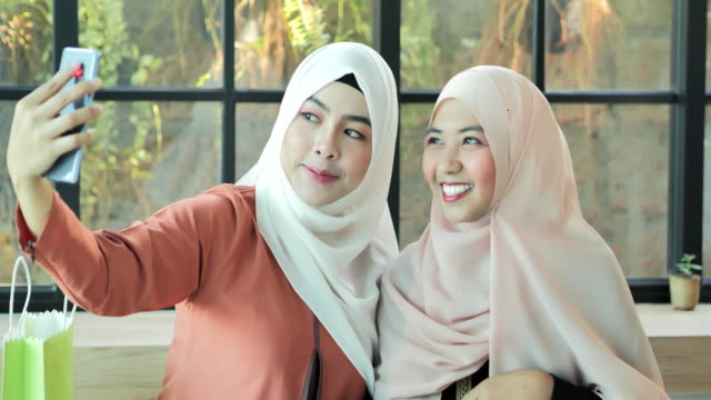two happy young muslim woman take self portrait with handphone.arab youth - cultura del medio oriente video stock e b–roll