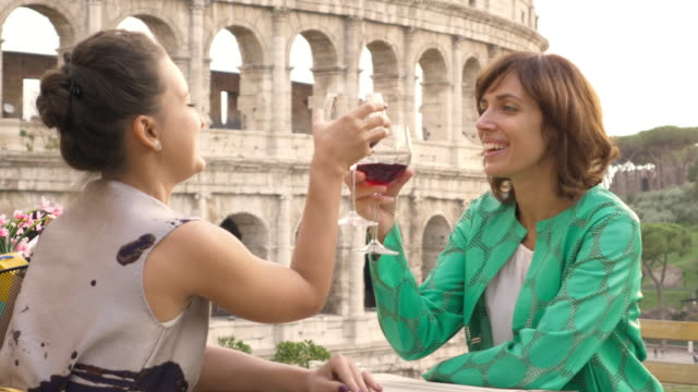 vídeos de stock e filmes b-roll de two happy young woman tourists sitting at the table of a bar restaurant in front of the colosseum in rome drink and toast with a glass of italian red wine. stylish colorful dress on a summer day at sunset - roma itália